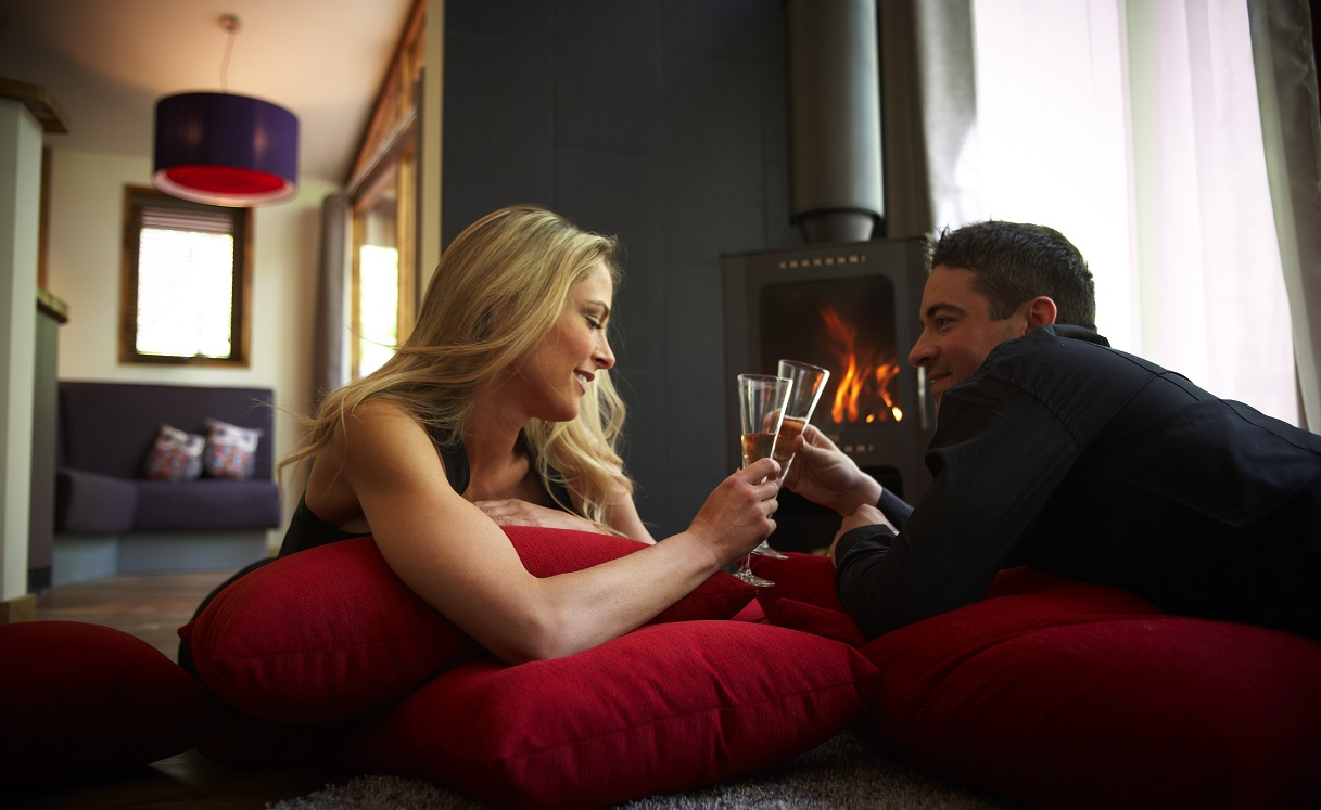 Couple relaxing by the log burner with champagne at Forest Holidays - Visit Nottinghamshire