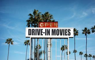 "A sign surrounded by palm trees which says, ""Drive-in movies, open""."